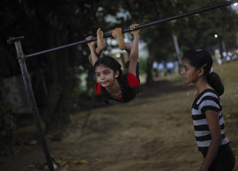 A girl exercises on a high bar during a gymnastics practice session at a park in Mumbai