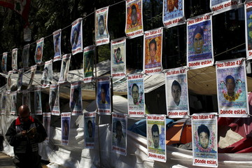 Pictures of the 43 students missing from Ayotzinapa College Raul Isidro Burgos are seen on a permanent camp as relatives take part in a meeting with Mexico's Attorney General Arely Gomez at the building of her office in Mexico City