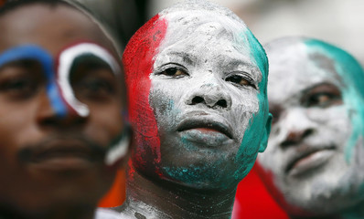 Fans celebrate with their faces painted with Guinea's Ecuatorial national colours inside Bata Stadium before the opening ceremony and soccer match of the African Nations Cup, in Bata