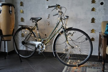 Bicycle decorated with lights in a room; object and interior concept.