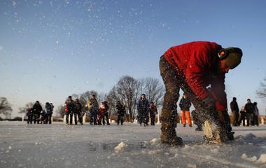 Jan Kuzel cuts an ice block to create ice sculptures on a pond of Dobra Voda