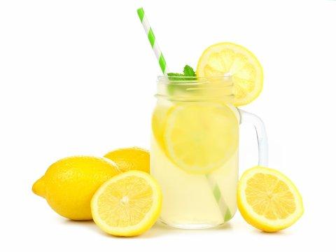 Mason jar glass of lemonade with lemons and straw isolated on a white background