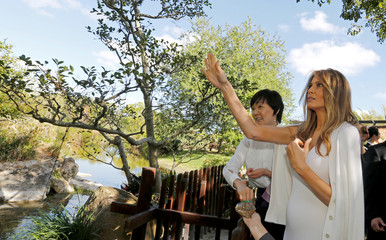U.S. First Lady Melania Trump and Akie Abe, wife of Japanese Prime Minister Shinzo Abe, feed Koi fish during a tour of Morikami Museum and Japanese Gardens in Delray Beach