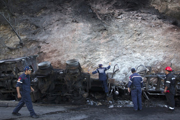 Firefighters inspect the wreckage of a burnt truck after an accident in Caracas