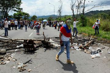 A demonstrator walks past a barricade during a rally demanding a referendum to remove Venezuela's President Nicolas Maduro in San Cristobal