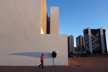 A man walks past a telephone booth at sunset in central Brasilia