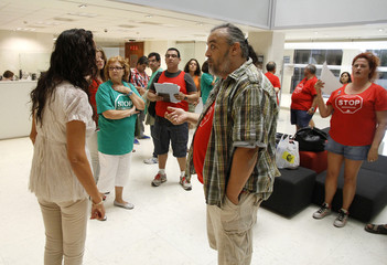A member of the Mortgage Victims' Platform argues with an employee as they occupy Bankia's central branch in Valencia