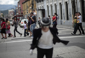 People watch Michael Jackson impersonator Marvin Romero dance on the streets of Guatemala City