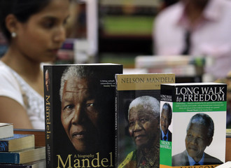A woman walks past a row of biographies of late South African president Nelson Mandela at a book shop in Colombo