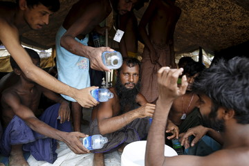 Migrants, who were found at sea on a boat, collect water at Mee Tike temporary refugee camp near the Bangladeshi border fence, outside Maungdaw township