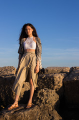 Young beautiful woman standing on the giant rocks on the beach