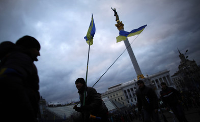 Protesters carry Ukranian flags as they walk near Independence Square in Kiev