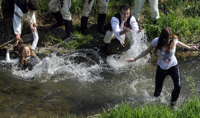 Slovak youths dressed in traditional costumes throw girls into a creek as part of Easter celebrations in the village of Trencianska Tepla