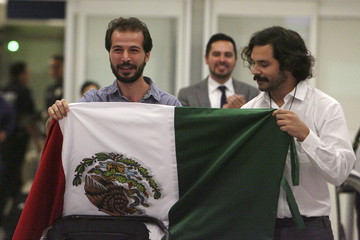 Syrian student Hassan holds a Mexican flag with Muzquiz, of the NGO Habesha Project, after his arrival to the Benito Juarez international airport in Mexico City