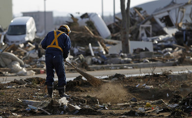 Worker cleans up at Sendai airport which was damaged by the March 11 earthquake and tsunami, in Natori