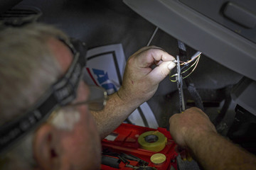 Technician Bob Poe works on wiring under the drivers seat of a Chevy Traverse because of a recall at Raymond Chevrolet in Antioch