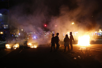Demonstrators gather around a street fire during a demonstration in Oakland