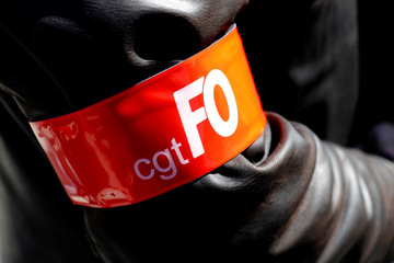 French Force Ouvriere (FO) labour union and French CGT trade union logos are seen on a security personnel armband are seen during May Day march in Paris,