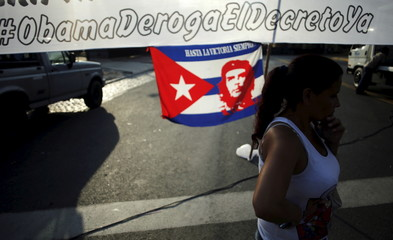 Supporter of Venezuela's President Nicolas Maduro stands next to a banner and a Cuban flag with an image of Che Guevara, during a demonstration outside the U.S. Embassy in Buenos Aires