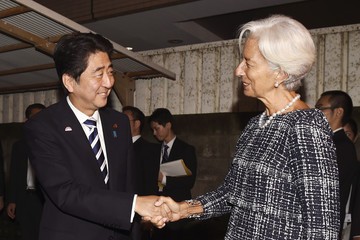 IMF Managing Director Lagarde is greeted by Japan's PM Abe at the entrance of the sushi restaurant Kozasa in Tokyo