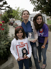 Rana, sister of Lebanese American Miss USA Rima Fakih, poses with her two daughters Elissa and Ogarit as they show pictures of her in Srifa