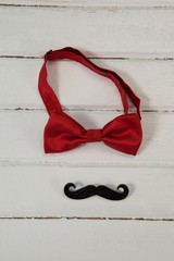 Bow tie and fake moustache arranged on wooden plank
