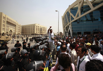 A demonstrator shouts anti-police slogans as protesters wait in front of a court where Egypt's former Interior Minister Habib al-Adli would be tried, in New Cairo