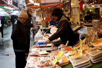 A shop clerk speaks to a shopper at a fish stall at a shopping district in Tokyo