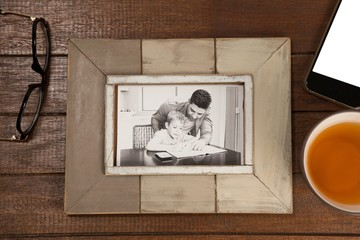 Photo frame, lemon tea and mobile phone on wooden plank