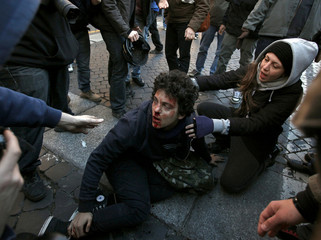 A demonstrator helps an injured fellow demonstrator during anti-government clashes near the parliament building in Rome
