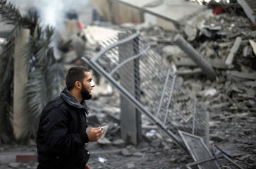 Wounded Hamas policeman guards the destroyed office building of Hamas PM Haniyeh after Israeli air strikes in Gaza