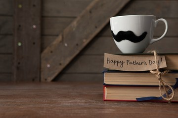 Cup with mustache kept on book stack