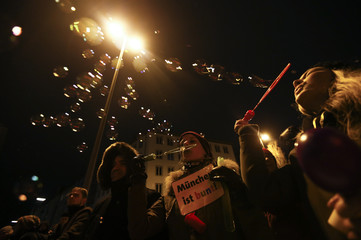 Opponents of the movement of Patriotic Europeans Against the Islamisation of the West (PEGIDA) hold a placard reading 'Munich is colourful' and make soap bubbles as they demonstrate in Munich