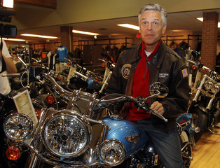 Former U.S. ambassador to China and possible Republican presidential candidate Jon Huntsman sits on a motorcycle at a Harley Davidson store in New Hampshire