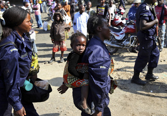 A newly deployed police officer carries her child in Goma port