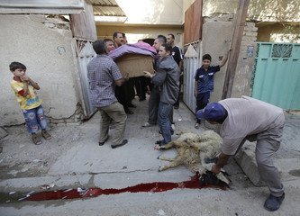A man slaughters sheep as others carry a coffin of a bomb attack's victim during a funeral in al-Shurta al-Rabaa district in Baghdad