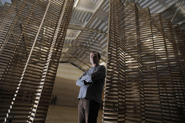 British artist Wilder poses for media before kicking  down his installation of 10,000 wooden slats 'Untitled # 155' at the Yorkshire sculpture park near Barnsley