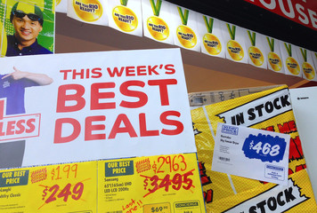 Sales posters are displayed at the front of a retail store selling electrical appliances in Sydney