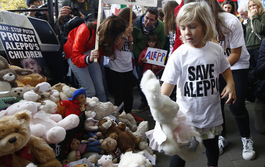 A child places a stuffed toy at the gates of Downing street during a demonstration urging the British government to intervene in the bombing of Aleppo, in London