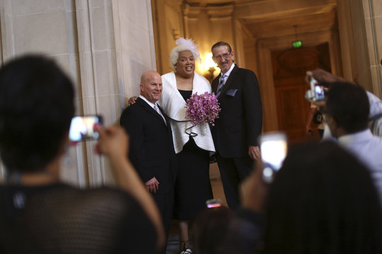 San Francisco Police Chief Suhr, poses for pictures with transgender activist Lee-Tillman and fiance Randy Dolphin prior to their marriage in City Hall in San Francisco