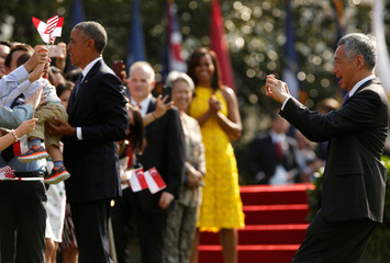Singapore's Prime Minister Lee Hsien Loong stops to take a picture as he and U.S. President Barack Obama greet visitors during an official arrival ceremony on the South Lawn of the White House in Washington