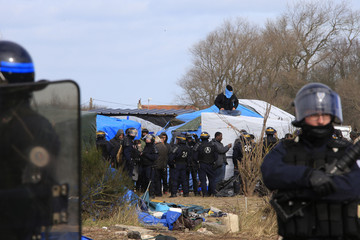 """French riot police secure the area as a migrant sits on his makeshift shelter during the partial dismantlement of the camp for migrants called the """"jungle"""", in Calais"""
