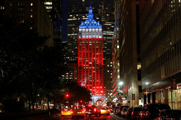 A couple photograph The Helmsley Building on Park Avenue lit in honor of the victims of the Nice attacks, in Manhattan, New York