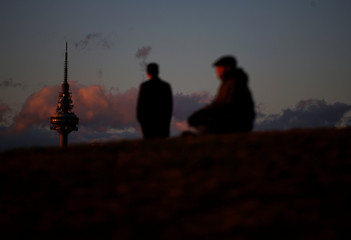 """The main telecommunications tower """"Torre Espana"""", known as """"Piruli"""", is lit by sunset as people sit on the top of a hill in a park at the end of a sunny winter day in Madrid"""