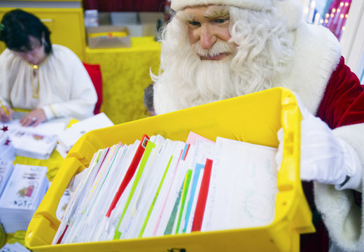 A man dressed as Santa Claus holds a crate of letters containing children's wish lists at the post office in the village of Himmelpfort