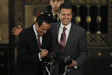 Marquez signs on a pair of boxing gloves which was used in Marquez's victory over Filipino boxer Pacquiao, and will be given to Mexican President Nieto, during a recognition ceremony at National Palace in Mexico City