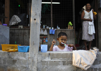 A child poses for a picture as he brushes his teeth in Yangon