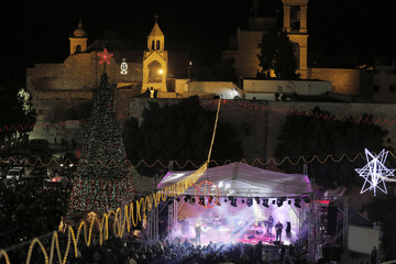 Musicians perform on stage in Manger Square, outside the Church of the Nativity, the site revered as the birthplace of Jesus, in the West Bank town of Bethlehem