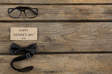Overhead view of happy fathers day text by eyeglasses and bowtie