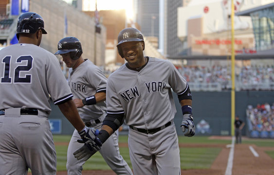 New York Yankees Cano is congratulated by on-deck batter Wells after he hits a two-run homerun against the Minnesota Twins during their MLB American League baseball game in Minneapolis